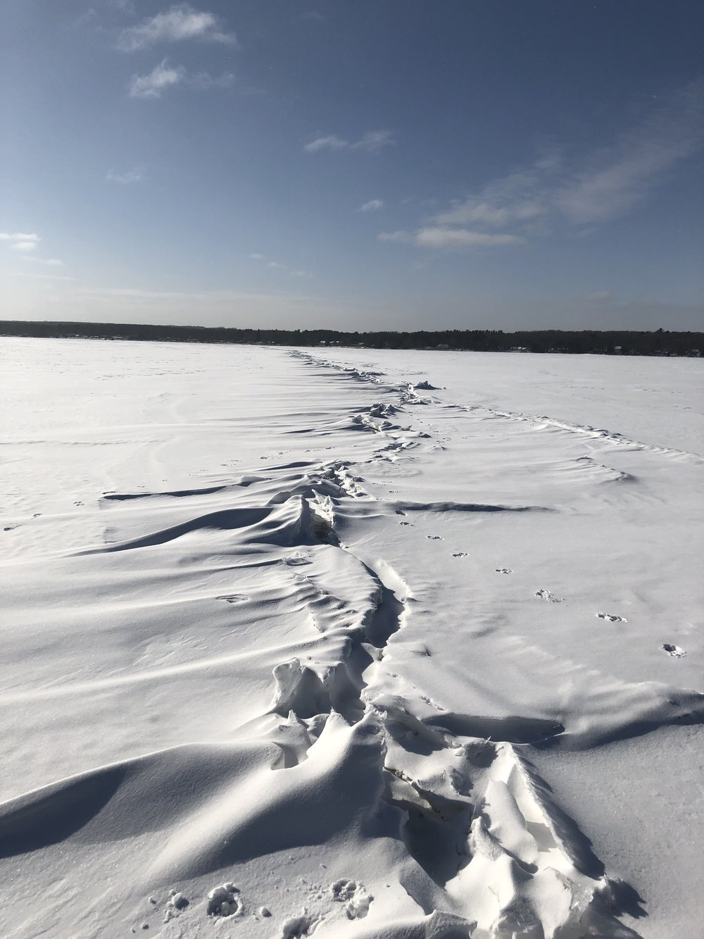 Like tectonic plates, two massive ice sheets from the opposing lobes of the lake meet and crumple across the entire breadth of the lake.