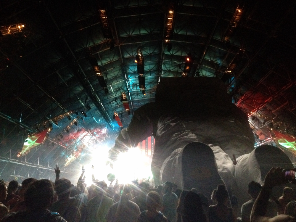 The astronaut can be found crowd surfing, amplifying the festival experience.