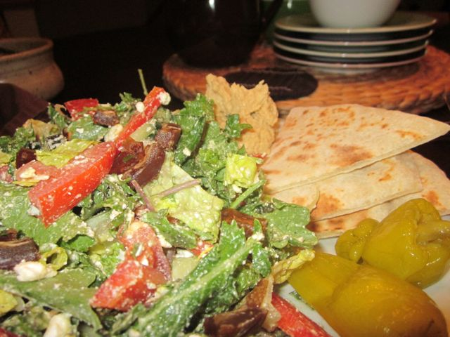 "Greek salad with ""power"" greens, tomato, onion, dates, cucumber, and feta. Pita, hummus, and pepperoncini are served on the side."
