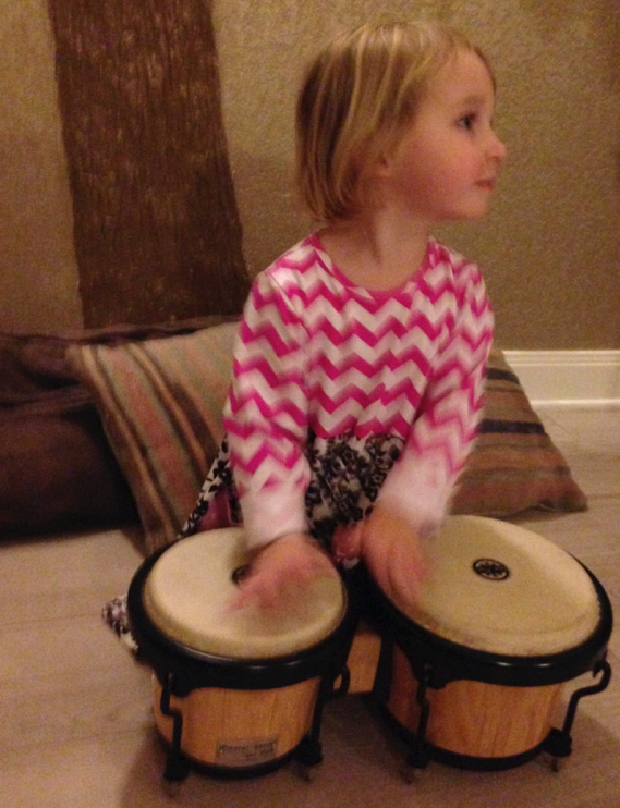 Clara is enjoying playing the drums during Bridge Prayer