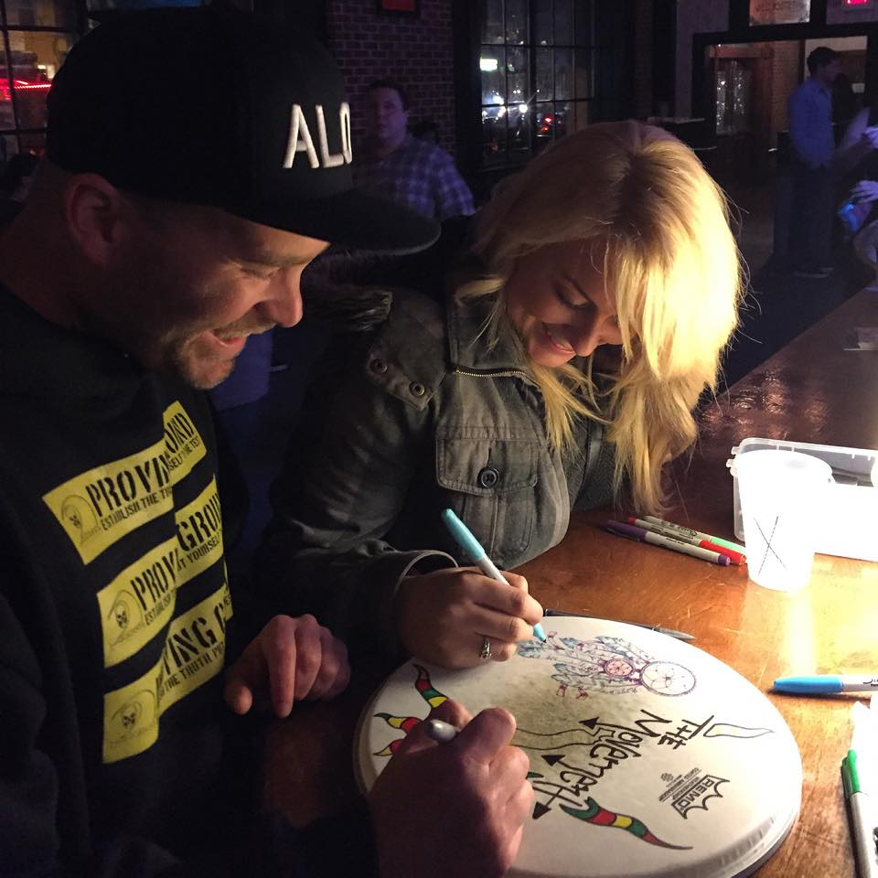 Joshua Swain of the Movement & Kc Cowan drawing on a drumhead with Sharpies