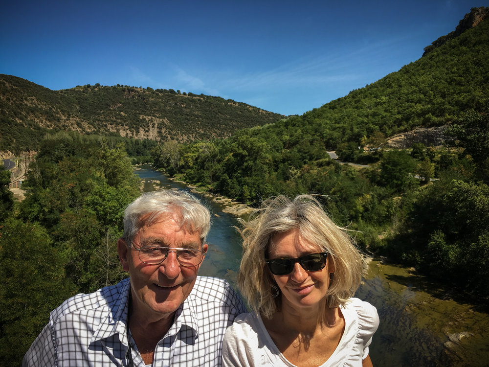 Gerry and Véronique facing the Millau Viaduct—a couple hundred metres away—the Tarn River flowing behind them.