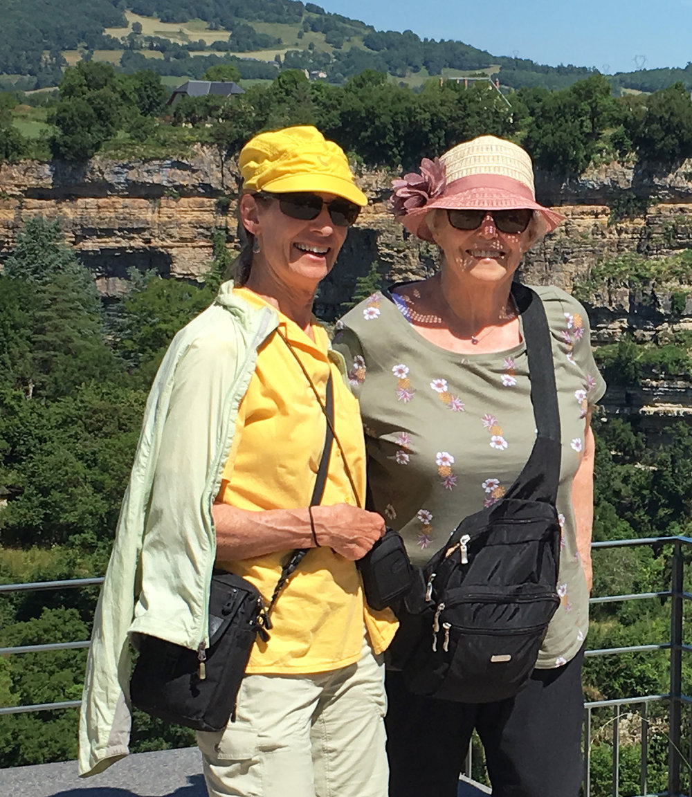 """Judith and Marilyn Kinsella enjoying the day. One of the day's highlights was a visit of the """"Trou de Bozouls"""". The amazing Bozouls village is perched on both sides of the cliffs' edges overlooking the Dourdou river and its gorges. Although seemingly a stream nowadays, the horseshoe-shape canyon was formed million years ago, and is 400 m (over 1300 ft.) in diametre and 100 m (over 300 ft.) deep!"""