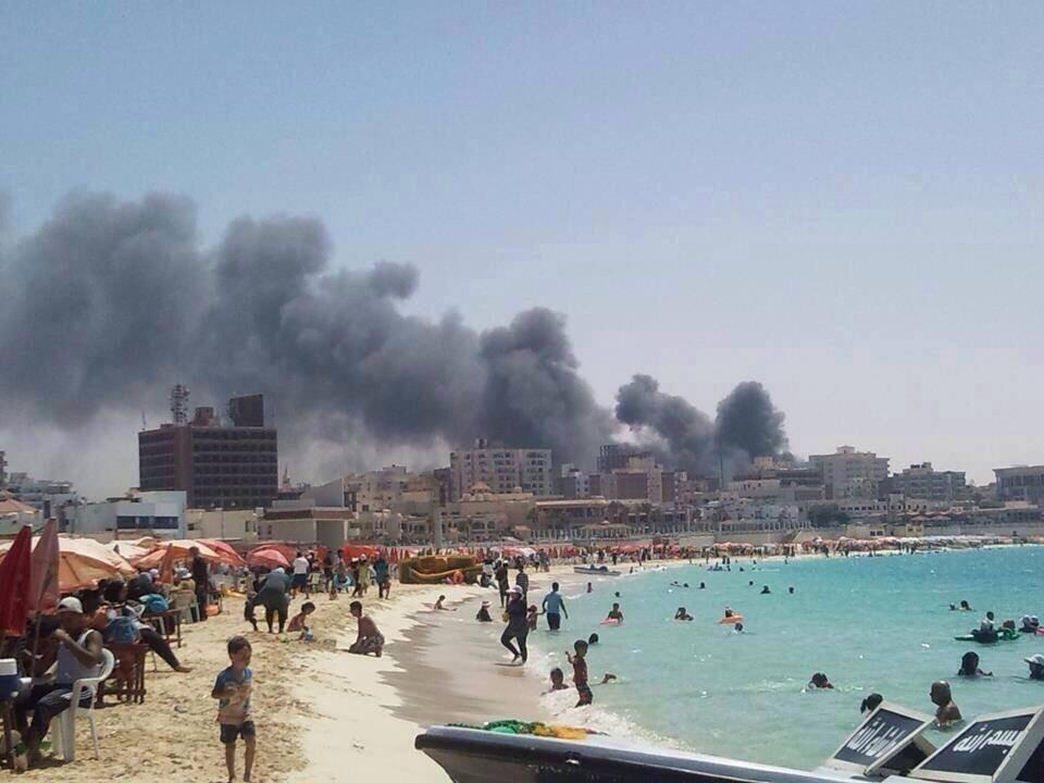 yassanova :     Egyptians at the beach as the city burns in the background. Absolutely surreal.