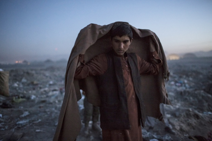 simply-war :     Nov. 14, 2012. An Afghan Pashtun boy, who said he was forced from the troubled province of Baglan due to threats from the Taliban, winds up his day after scavenging for recyclables at a garbage dump site in Kabul.Daniel Berehulak.