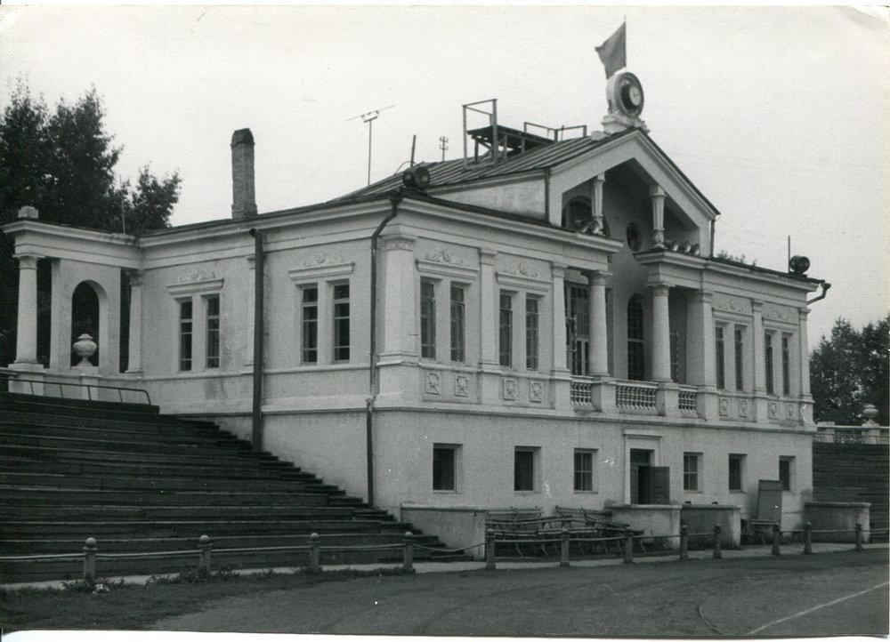 Het hoofdgebouw in vroeger tijden met de klok boven op het puntdak.