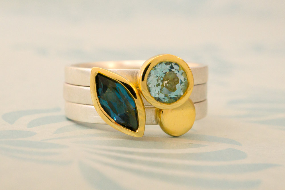 Stacking ring trio. Marquise shaped London blue topaz and round sky blue topaz set in 18 carat yellow gold, and gold nugget all on silver bands