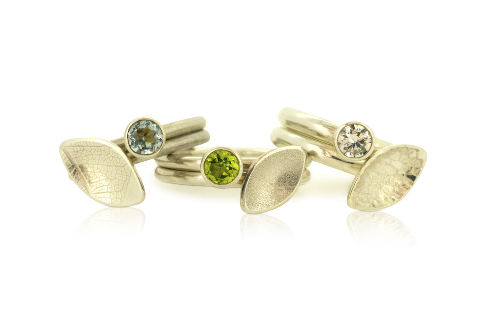 Three pairs of falling leaves stacking rings with blue topaz, peridot and cubic zirconia
