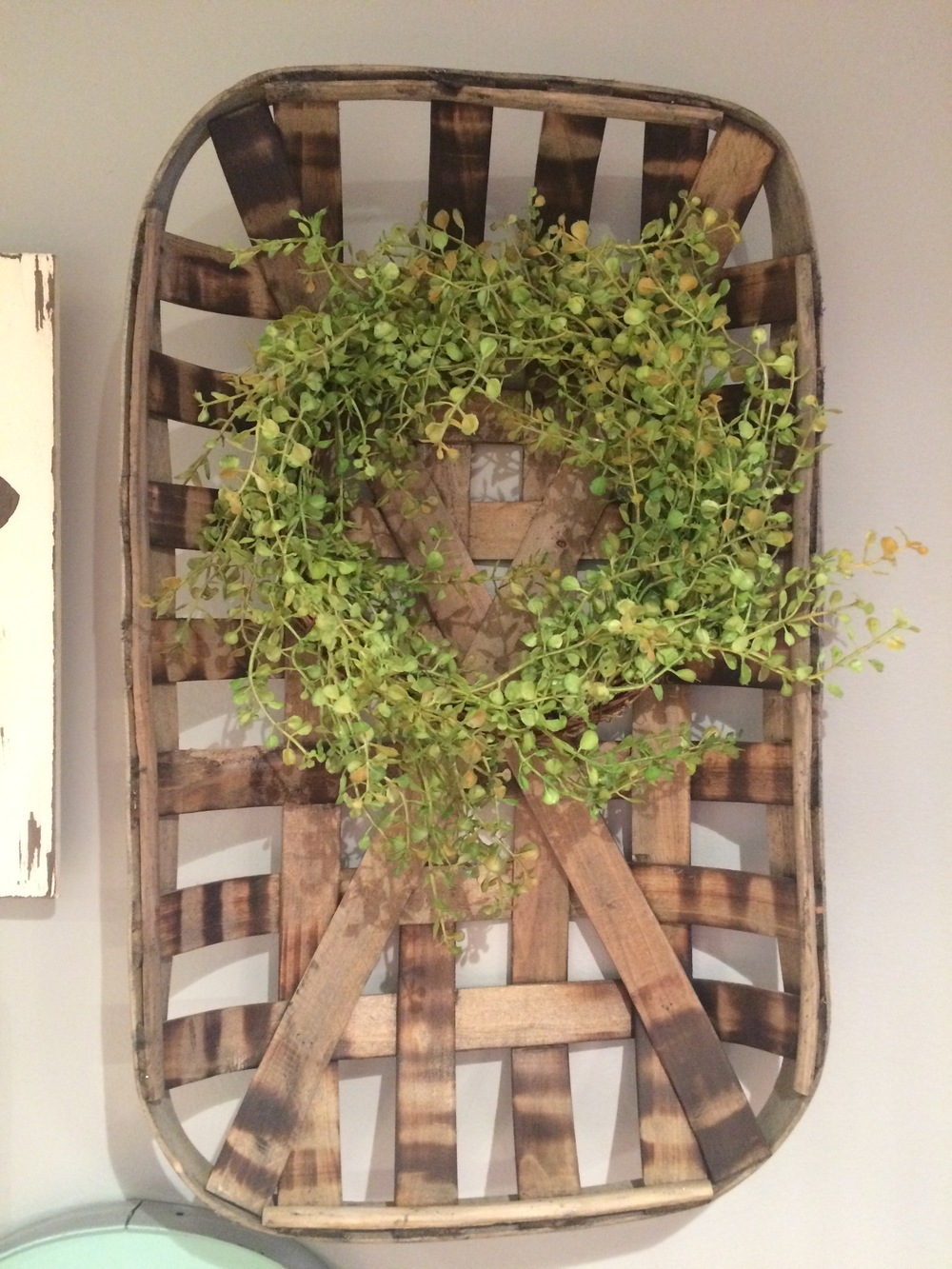We added some color to this old basket hanging on the wall with a sweet little green wreath.    Photo from: Chrysy Huff