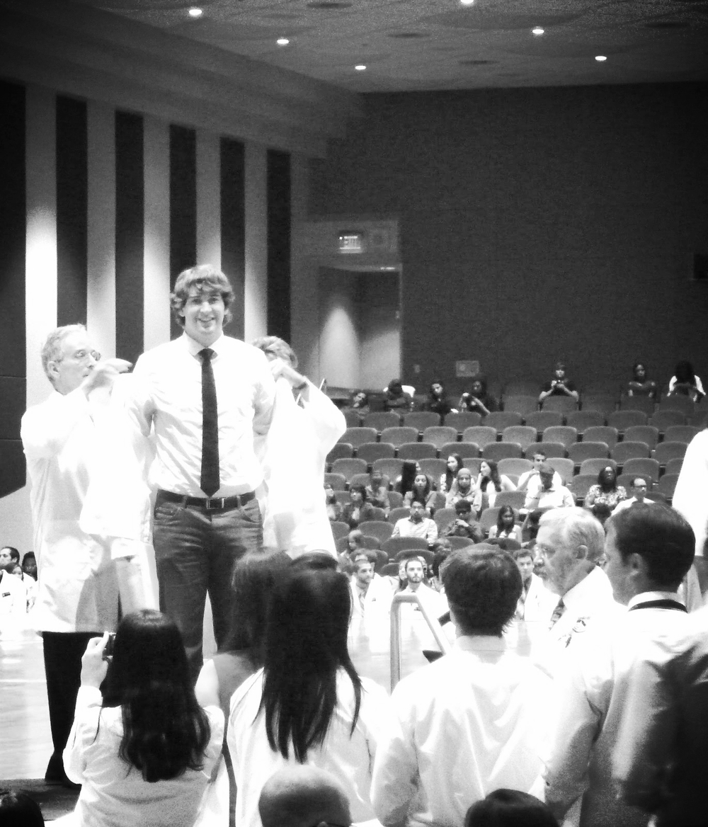 Kevin being sworn in at his white coat ceremony, a couple months after medical school began. The coat didn't fit well then, and it fits even worse now.