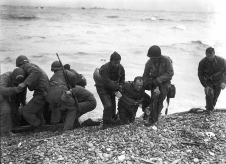 George and another soldier helping a comrade onto the beach in Normandy. He is the one without a helmet.