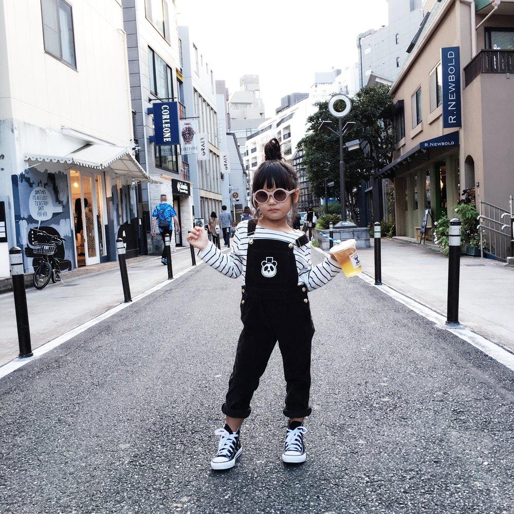 In the middle of CAT STREET in Harajuku:Shirt: Emile Et Ida from Minou Kids, Overalls: Mini Rodini from Minou Kids, Sunnies: Winkniks, Sneakers: Converse