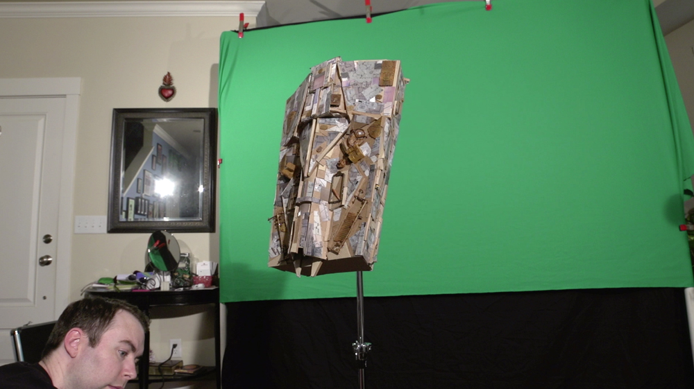 The Miniature Spaceship being shot against green screen. This ship was made from foam-core, cardboard, 3D printed parts, found objects, battery operated christmas lights, and model car parts.