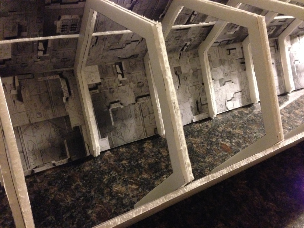 Here is a work in progress shot of the miniature spaceship corridor.  It was designed with foam core. Photographs were taken of a cardboard wall, printed out, and glued on. It was later dramatically lit with flashing lights.