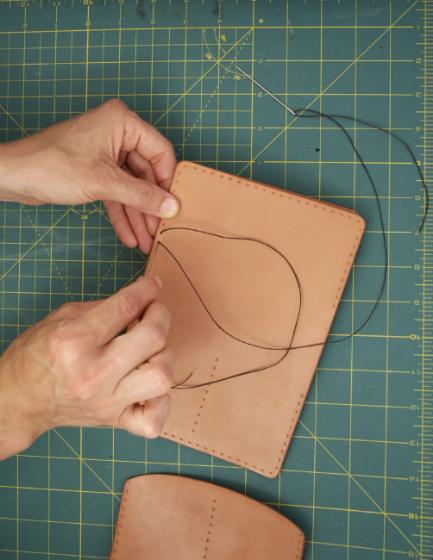 10. Flip leather over and insert other needle into the same hole and pull through hole.