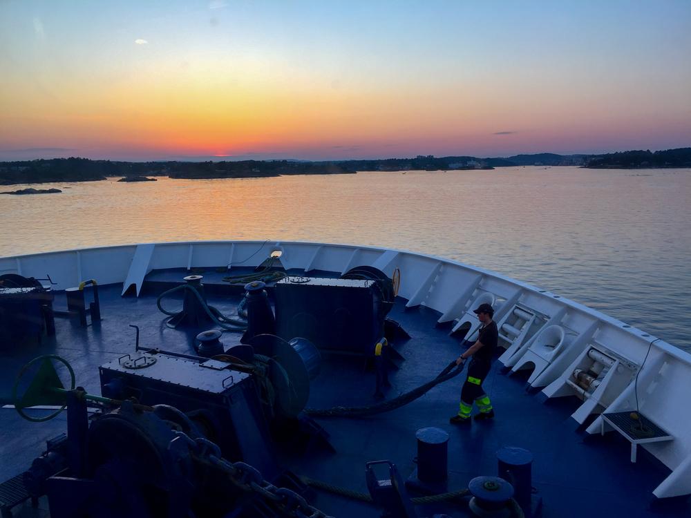 En matros utfører siste arbeidsoppgaver i det Color Viking seiler inn i Sandefjordsfjorden