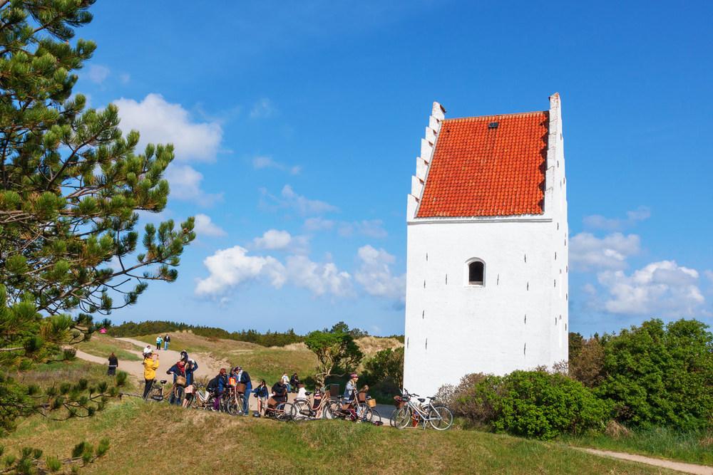 Når du er i Skagen, så besøk denne originale kirken med en høyst uvanlig beliggenhet, der kirkebygget står omgitt av sanddyner.