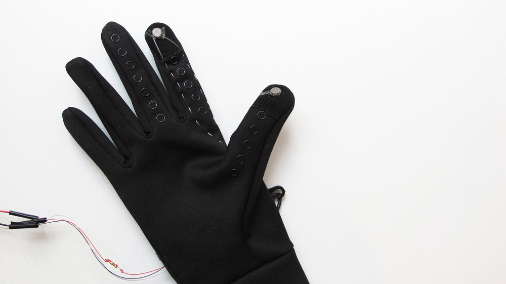 "The gloves we used came with ""touch pods"" that work with a mobile screen.    We modified them into contact switches using conductive thread."