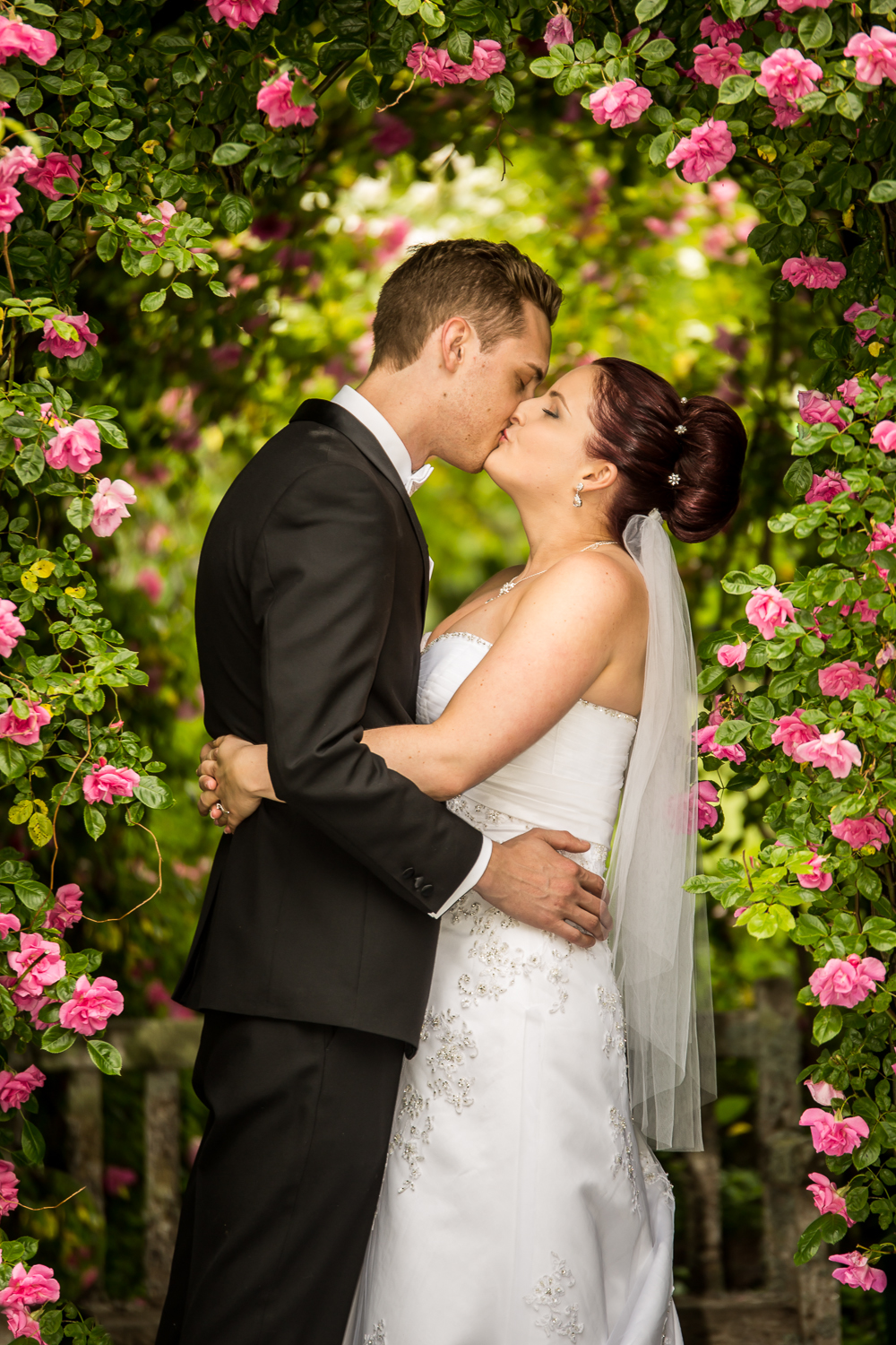 Bride and Groom under the roses.