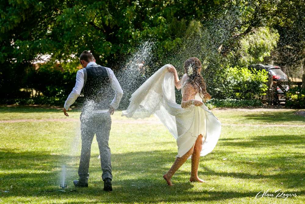 Bride and Groom cooling off under the water sprinkler.