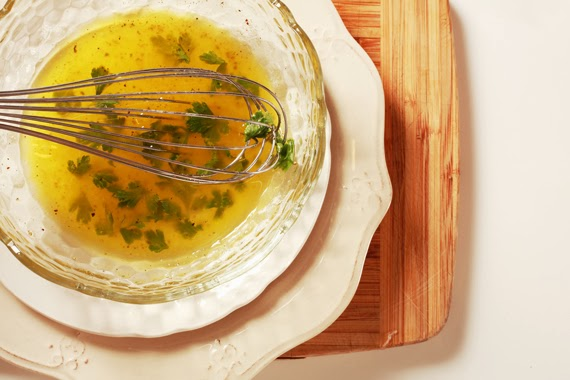 5. 取一玻璃碗,倒入檸檬汁、撒上巴西里、再加入橄欖油,並撒上少許鹽巴、黑胡椒拌勻。