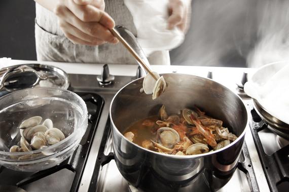 2. 以中小火炒至蝦殼變色後加入白酒,蛤蠣殼一開了就要取出備用不要煮過熟會失去口感。煮至酒精蒸發後放入水(蓋過材料即可)煮約15分鐘。將高湯過濾後備用。