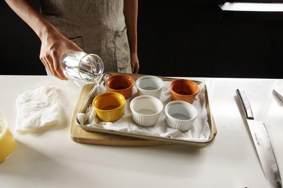 5. 烤盤內可以放入一塊布或是報紙後加入水(份量外)。如果是溫水就更好了! 這個的原理是法式烤布蕾需要以低溫烘烤讓它定型,烤盤中注入水可以讓底盤溫度穩定,放一塊布則是讓滾沸的水不會四濺。