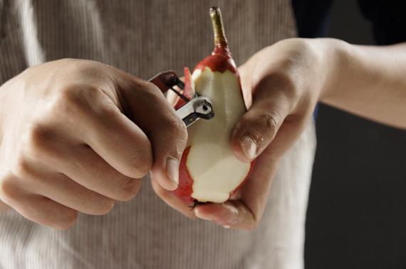 2. 趁著在煮酒時,將洋梨削皮留下莖(可見圖示),削完會洋梨開始氧化,建議可以泡在水裡。放入所有處理好的梨子蓋鍋以小火微微沸騰的狀態與其他材料煮約40分鐘。如果洋梨的數量比較少,酒汁沒有蓋過梨子,就要適時的翻面。