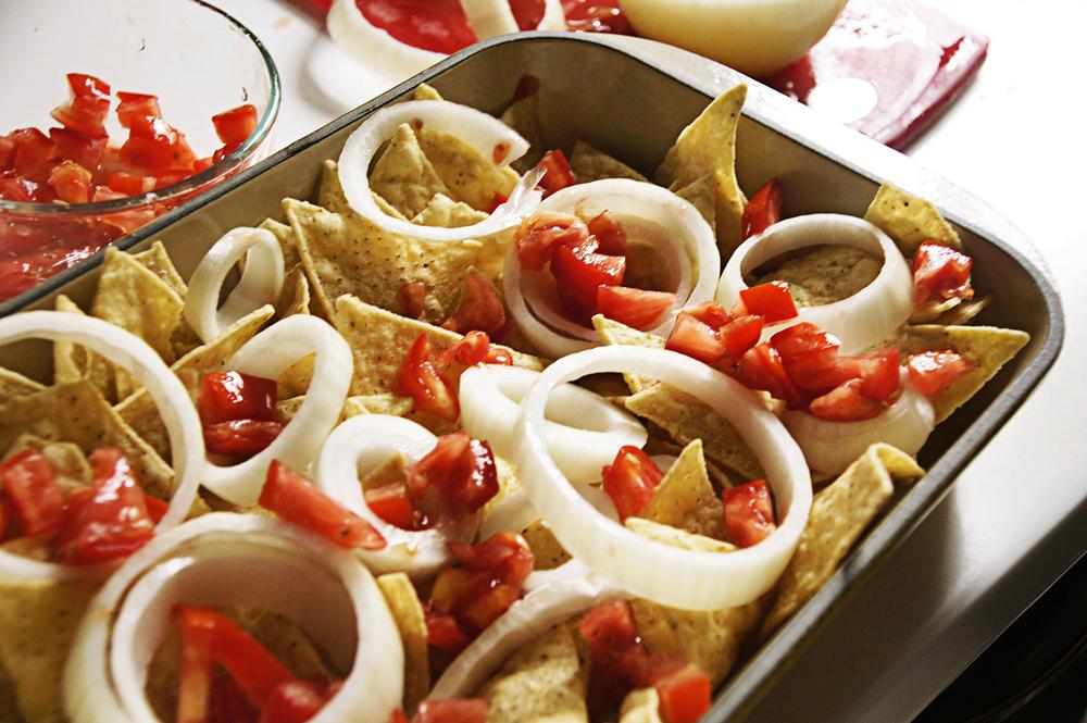 4.在烤皿中放入玉米脆片、洋蔥圈圈,少許醃辣椒切片,淋上適量的肉醬,放上起司絲,200 度烤箱烤約1-2分鐘,出爐後放上新鮮的番茄丁、酪梨丁,就完成這道玉米脆餅佐墨西哥辣肉醬!進烤箱前的組合份量可以依照你自己喜歡的比例安排,喜歡起司牽絲的感覺就多放點起司、喜歡肉醬味道濃一點就多挖一點 。