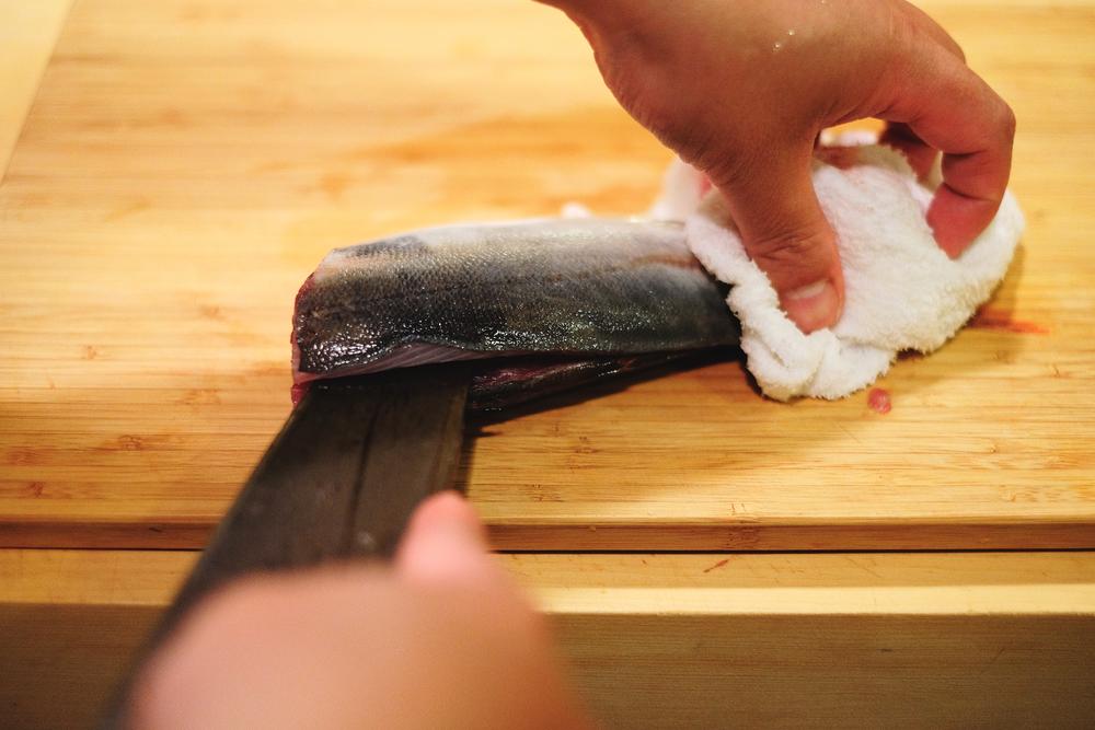 4. 翻到另一面,用布壓住魚尾,將刀尖往身體內一點,再用力地從魚尾往魚身畫開