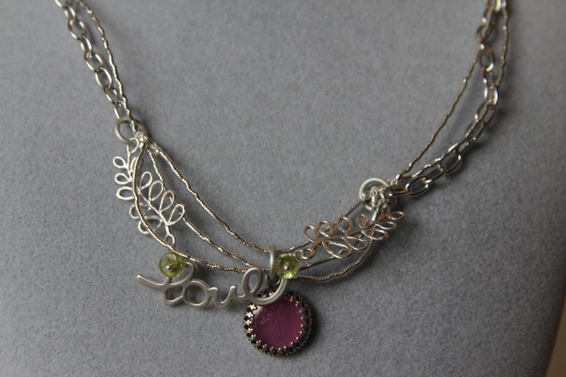 Strings Attached (ruby, peridot, sterling silver, rhodium plated brass, silver thread, cotton)