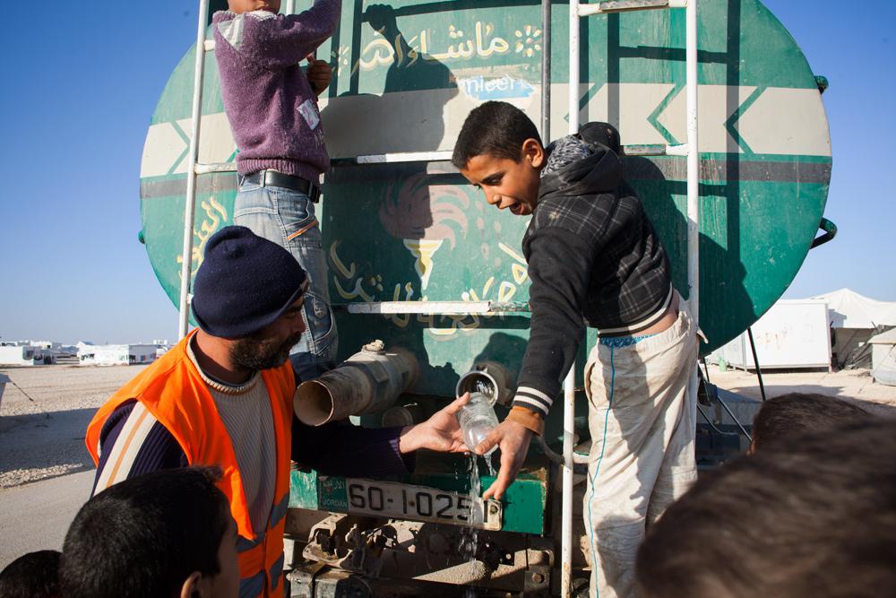 The water truck passes through district 4 of Zaatari refugee camp.