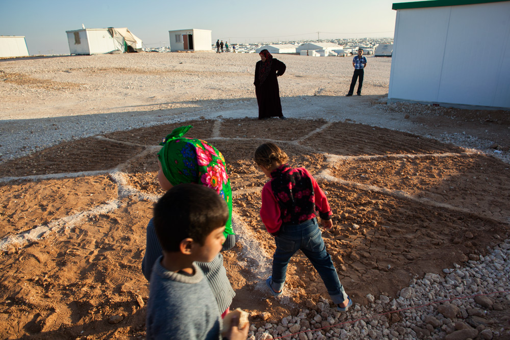 Kids play near a newly planted community garden in a corner of district 4 in Zaatari refugee camp.