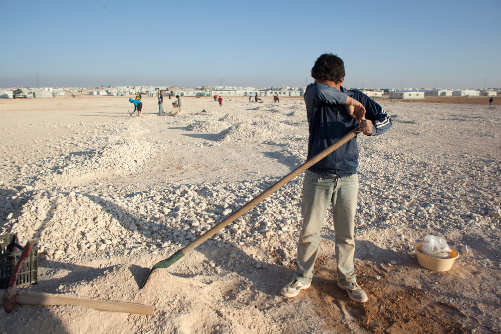 A teenage boy takes a break while sifting stones from sand to make concrete blocks in the Jordan desert at Zaatari.