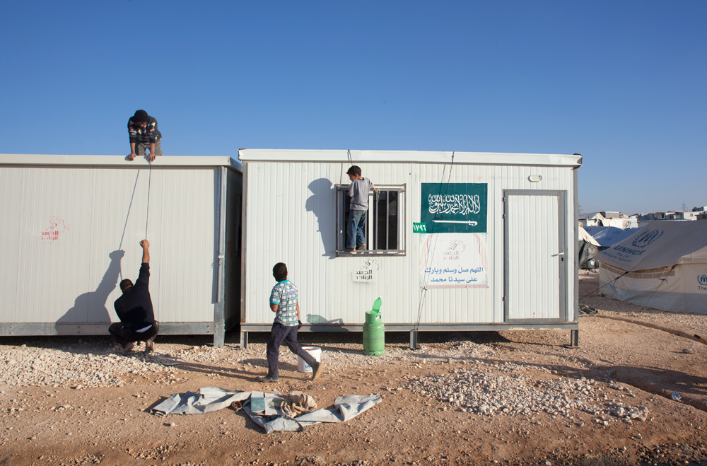 Men and boys work at securing new cabins in the middle of Zaatari refugee camp. Cabins are being replaced by tents for living by the UNHCR to try to give some sort of sense of normalcy and comfort to people who have been living long term at the camp.