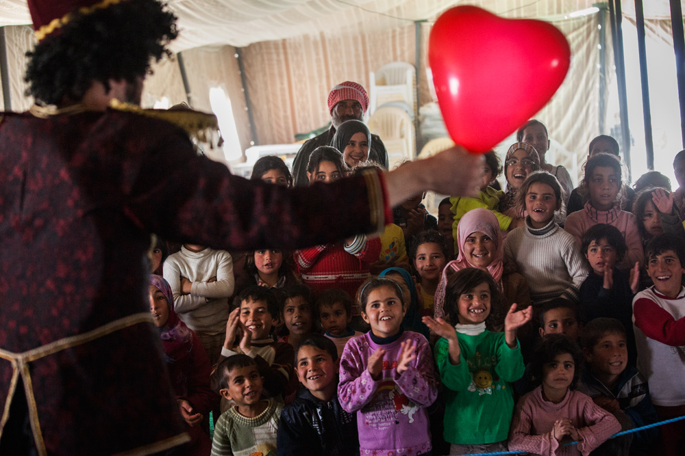 Momo the clown from Clowns Without Borders Ireland impresses Syrian children with his heart balloon trick at Zaatari refugee camp.