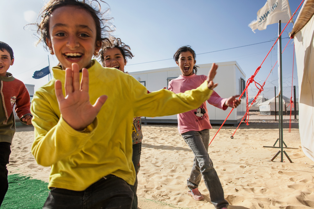 Children at Zaatari rush to enter a UNHCR tent where a Clowns Without Borders Ireland show is about to commence.