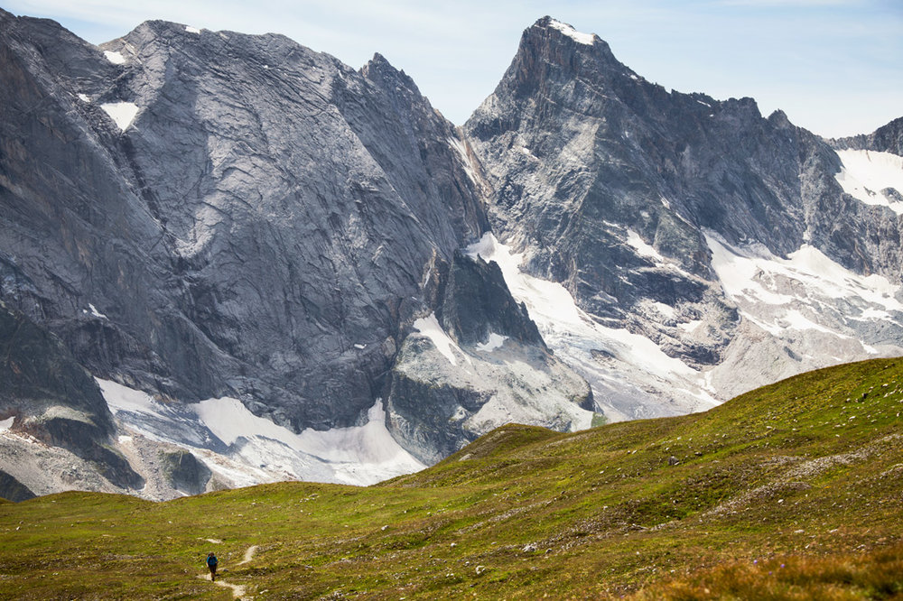 Seen from the Col de la Grassaz, the peaks of the Vanoise Massif tower over a lone hiker. The parks sees up to 360,000 visitors a year and is surrounded on all of it's borders by some of the largest ski resorts in the world.