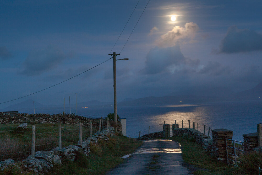 Moonlight illuminates the island's only road and the expanse of Clew Bay to the east.