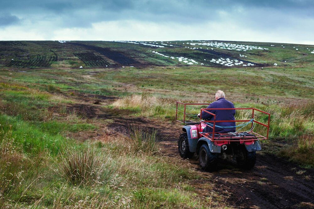 Heading out on the bog to lift bagged turf. ATVs are gradually replacing the tractor as the most efficient way to get bags of turf off the bog as quickly as possible. They are also less prone to sinking in the soft water logged land. Before mechanization the horse and cart was the traditional method of bringing in the turf and many older people talk of those days when the task moved a lot slower.