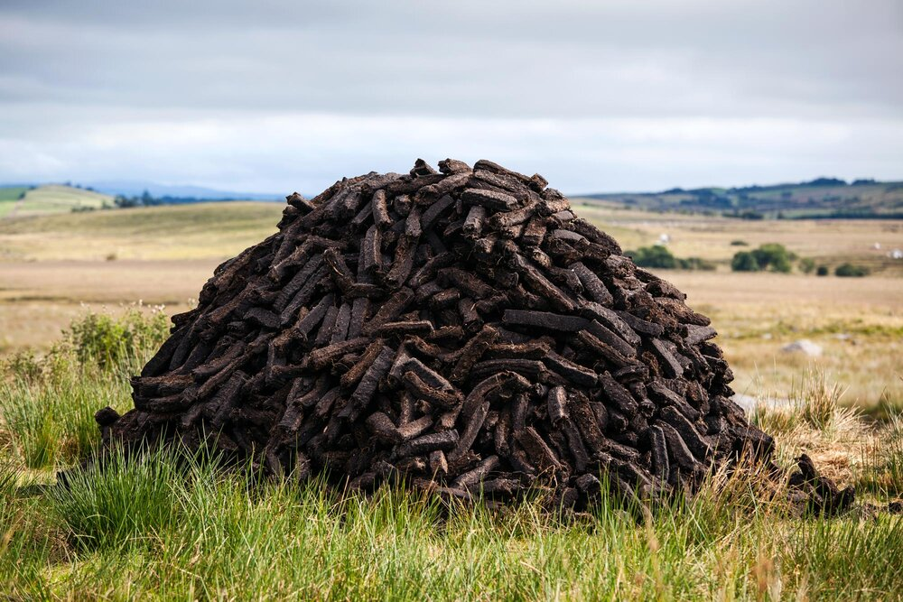 Turf Stack on a bog in County Mayo. In the west of Ireland the turf is stacked into mounds on the edges of the bog and taken off in trailer loads. In other parts of Ireland mounds like this are notably more absent and the turf is bagged directly on the bog.