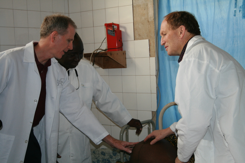 Dr. George Mulcaire-Jones and Dr. Bob Scanlon with a patient in Sierra Leone