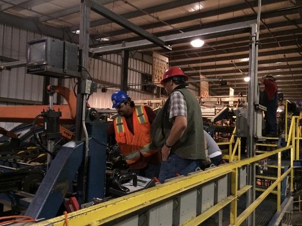 Joe Young (left) and Kelly Olney look over some machinery at the Large Saw Mill Planer