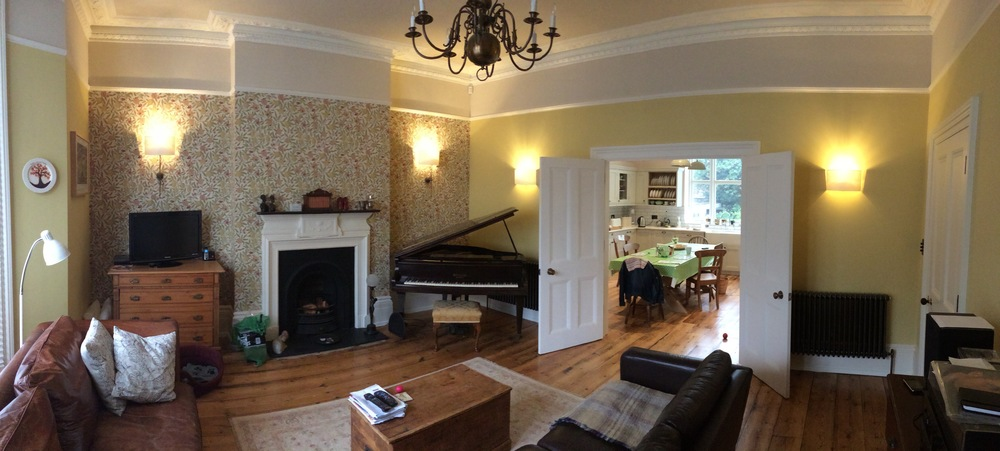 Living room with original floorboards refurbished and opening created between living room and new kitchen.