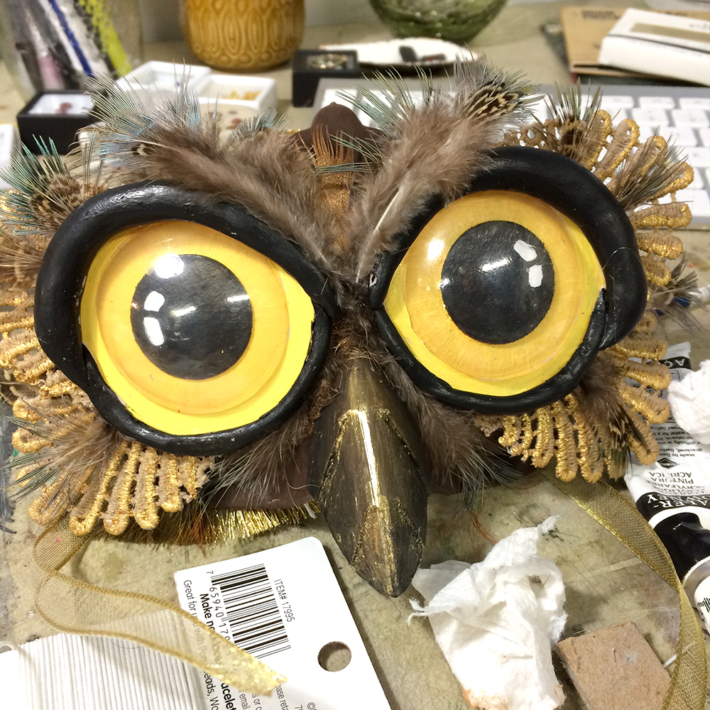 Almost there. strategically placing & gluing feathers. At this point, I stepped back and couldn't stand the look of the eyes. They were far to bold and angry. I ended up mixing up gold and black glaze to tone them down a bit. I also used this glaze on the lace & beak.