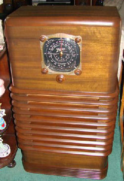 1937 Zenith 6S157 Zephyr Console tube radio. This is a superb example of the American Art Deco era for the late 1930's. This is the rare 6 tube radio model 6S157. A 10 tube version was produced as well. It was designed by John Stevens and is one of the most distinctive looking radios produced by Zenith. John Stevens design created a very simple wood cabinet, with heavy rounded edges and deep horizontal louvers that encircle the sides of the cabinet. This most distinctive design resulted in the Zenith Zephyr radio line up for 1937. The radio has the original Zenith wood knobs. The dark black walnut veneered cabinet is beautifully restored with a flawless lacquer finish and trimmed tones. The grille cloth is a reproduction of the original pattern. Every detail was reproduced to keep the original look.