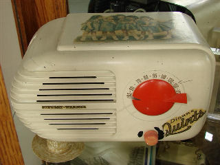This is a 1940 Stewart Warner Dionne Quints radio. This radio case is broken and glued back together with no missing pieces. I can just picture what most likely happened. It was likely the radio was in a little girls room and a pillow fight took place. The radio fell form the night stand. Crying and crying took place and dad glued it back together. Also she must have scratched marks on the dial for her favorite stations, or dad could have because she was too young to get the hang of finding the stations. The paint is worn around the on/off volume control because her finger nails were to long. OK I'm making this up... but it could have happened. It gives it some personality. Or a reason for the marks and breaks.