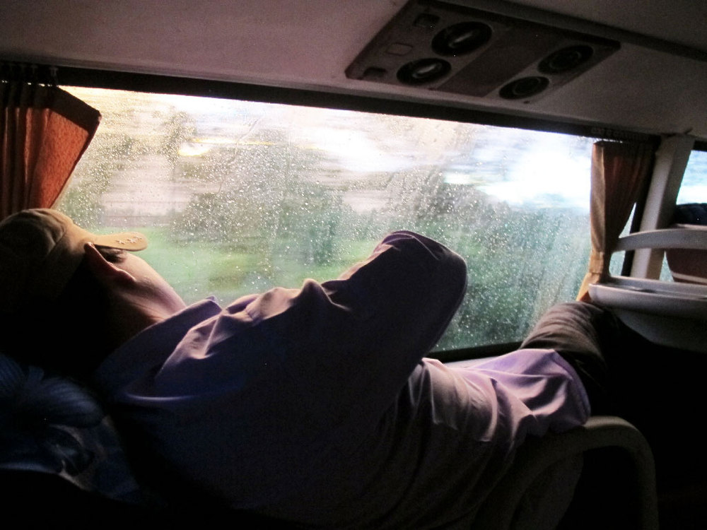 Melancholic bus traveler looking out the window with raindrops #vietnam / sergivich.com