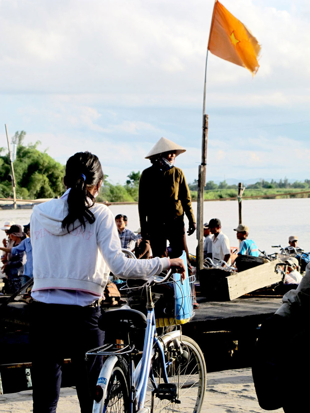Vietnamese girl with bicycle with vietnamese holding a #VetnamVietnam flag / sergivich.com