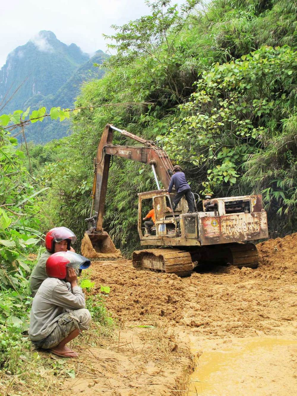 Cleaning the road with a bulldozer while two drivers waiting in #laos / sergivich.com